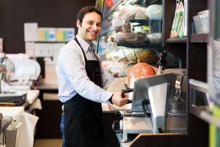 Shopkeeper cutting ham in grocery store