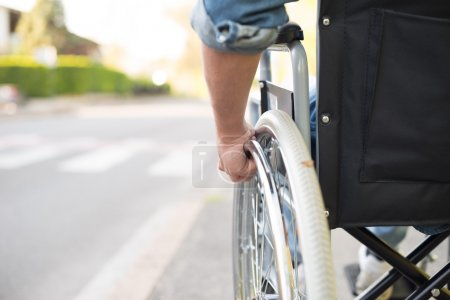 Man in wheelchair preparing to go across the road