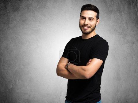 Photo pour Portrait d'un jeune homme souriant sur fond grunge - image libre de droit