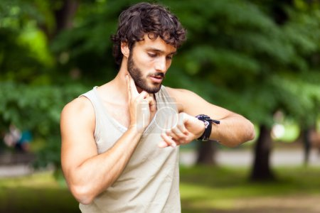 Photo for Male runner looking at sports smart watch during workout outdoor - Royalty Free Image