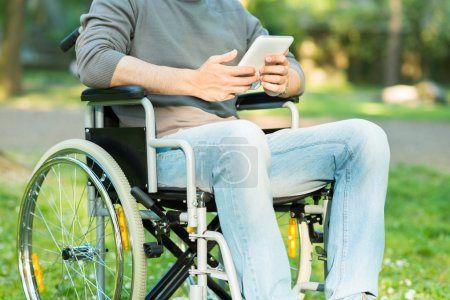 man using tablet on wheelchair