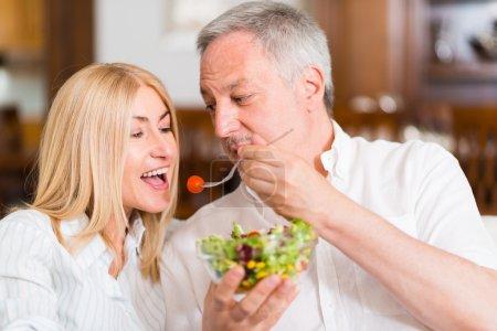 Mature couple eating salad
