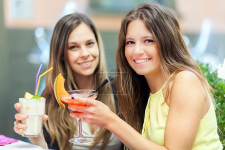 two friends drinking a cocktail