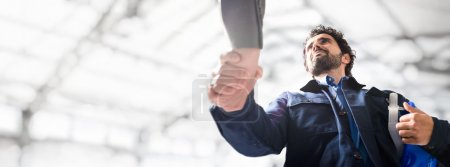 Photo pour Verticale d'un ingénieur donnant une poignée de main, grand espace de copie - image libre de droit