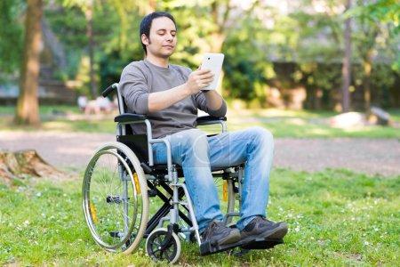 man using a wheelchair in a park