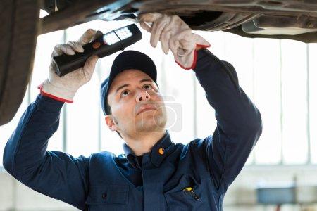 Mechanic inspect a lifted car