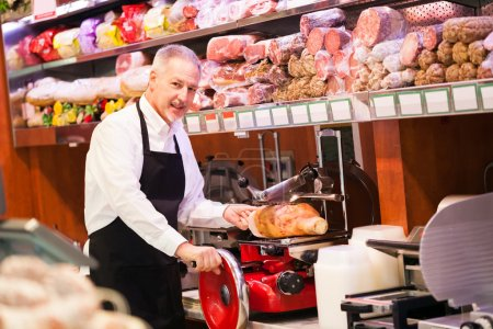 Shopkeeper cutting ham
