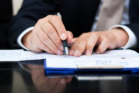 Businessman writing  document in office