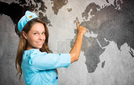 smiling stewardess in front of a world map