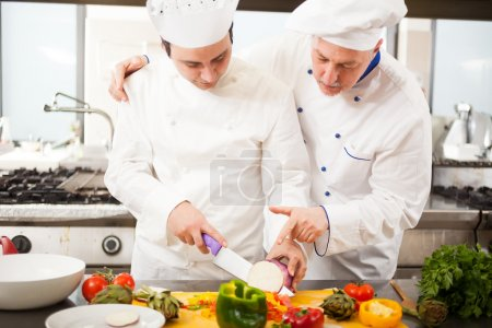 chef watching his assistant cutting vegetables