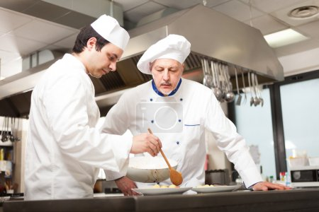 chef watching his assistant garnishing a dish