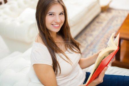 Photo pour Jeune femme souriante lisant un livre dans sa maison - image libre de droit