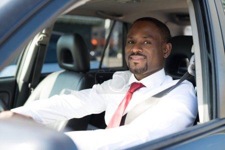 Photo pour Portrait d'un bel homme d'affaires souriant conduisant sa voiture - image libre de droit