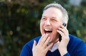 Starší pohledný muž mluví na telefonu