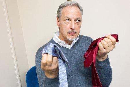 man choosing between two neckties