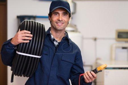 Photo pour Portrait d'un travailleur souriant portant un conduit ondulé et un testeur - image libre de droit