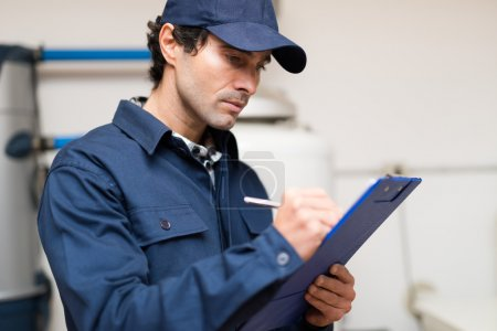 Photo for Technician fixing an hot-water heater - Royalty Free Image