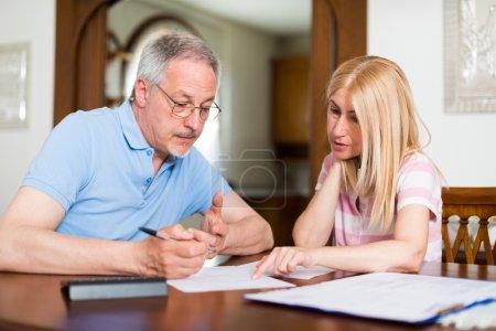 Photo pour Couple d'âge mûr calculant leurs dépenses ensemble - image libre de droit