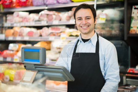 Smiling shopkeeper in a grocery store