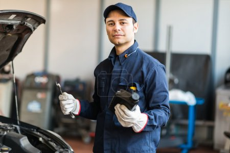 Auto mechanic holding a jug of motor oil