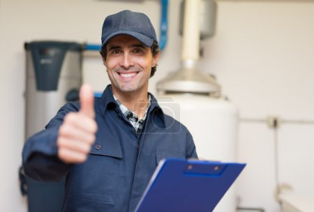 Photo for Smiling technician servicing a hot-water heater - Royalty Free Image