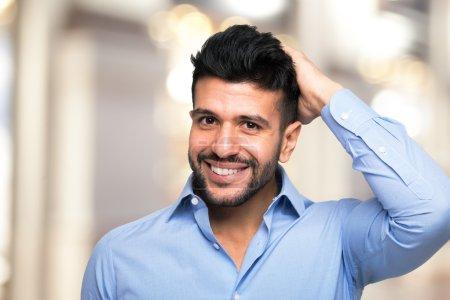 Photo pour Portrait d'un homme de toucher ses cheveux - image libre de droit