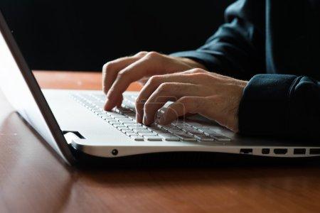 Photo pour Mâles mains tapant sur un clavier d'ordinateur portable - image libre de droit