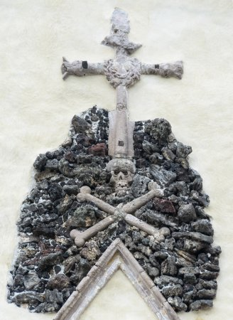 Skull on a pile of stones on which rests a cross.