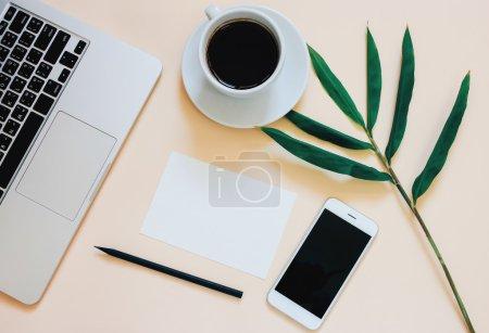 Photo pour Creative photo plat laïc du bureau espace de travail avec ordinateur portable, smartphone, café et papier blanc avec le fond de l'espace de copie, style minimal - image libre de droit