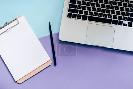 Photo for Top view flat lay style of worksapce desk with laptop and blank clipboard on minimal color background - Royalty Free Image