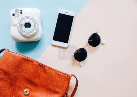 Photo pour Pose plate de sac femme en cuir marron ouvert avec accessoires, appareil photo instantané et smartphone sur fond coloré - image libre de droit