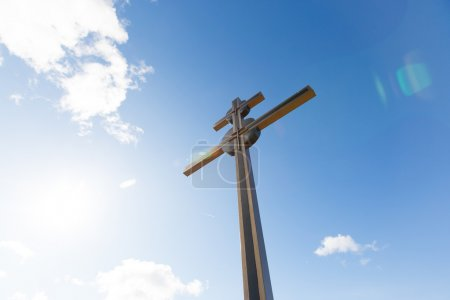 Cross and sunny sky background