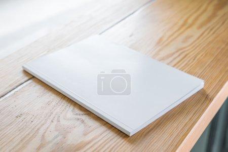Photo pour Catalogue ou magazine vierge, maquette de livre sur fond de table en bois - image libre de droit