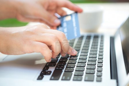 Photo pour Mani tenendo una carta di credito e utilizzando il computer portatile per lo shopping online - image libre de droit