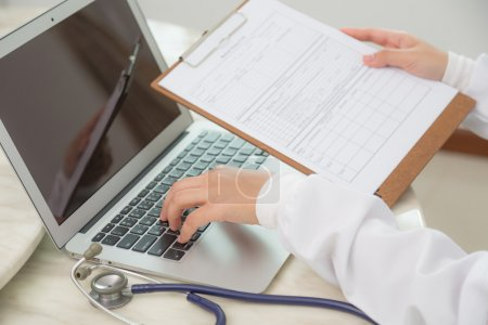 Doctor hands typing on laptop keyboard