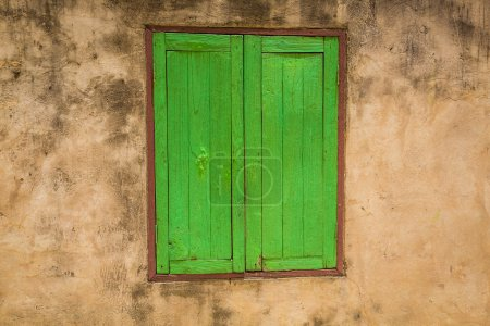 Green window on a old  wall