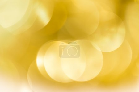 Abstract sparkling defocused light bokeh on gold background