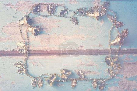 Photo pour Chaîne cloche en or de Noël décorative sur fond en bois bleu grunge - image libre de droit