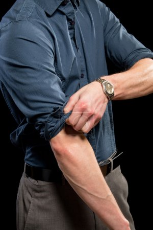 Foto de Hombre adulto rodando encima de sus mangas. Estudio disparó sobre el negro. - Imagen libre de derechos
