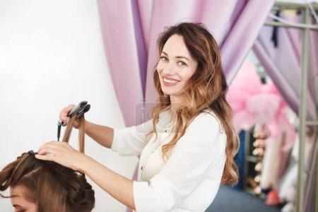 Photo pour Coiffeur fait fille coiffure avec de longs cheveux bruns dans le salon de beauté. Créer des boucles avec des fers à friser. Contenu des soins capillaires professionnels. - image libre de droit