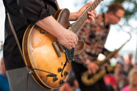 Photo pour Homme avec guitare au concert en plein air - image libre de droit