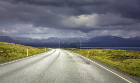 Curved asphalt road in high mountains of Iceland