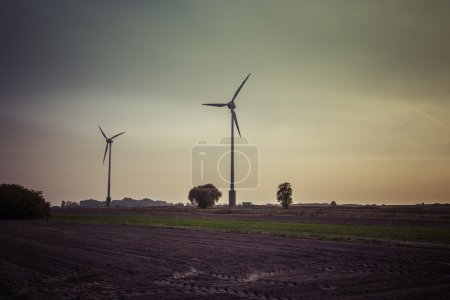 Wind turbines silhouette in the sunset sky