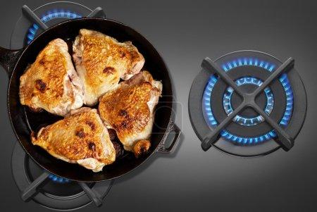 Photo pour Pan fried chicken on the gas stove top view - image libre de droit