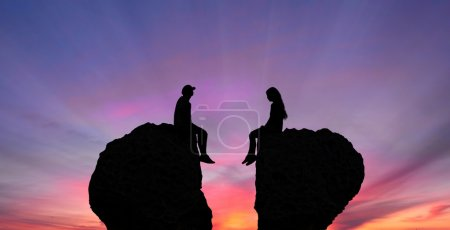 Photo for Young couple in quarrel sitting on rocks shaped as broken heart - Royalty Free Image