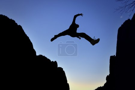 Photo for Man jumping over precipice between two mountains - Royalty Free Image