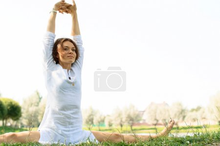 Young attractive woman practicing yoga outdoors.