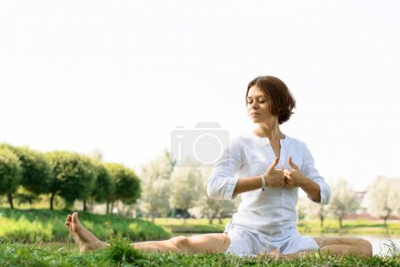 Girl in white clothes practicing yoga at the river-bank