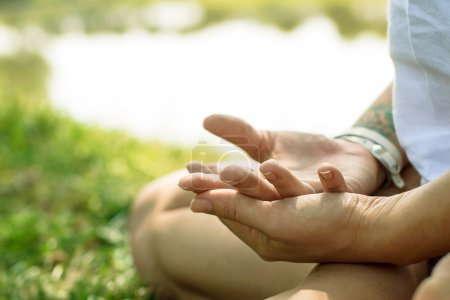 Closeup of female hands put in yoga mudra. Woman is meditating at the river-bank