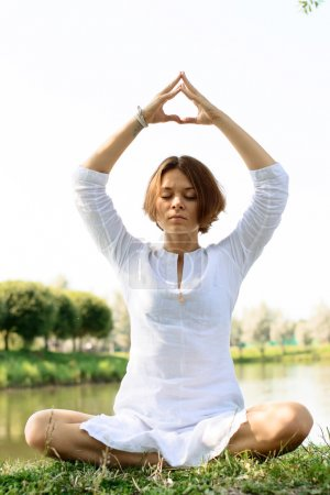 Woman in meditation pose. The hands in put in mudra are places above the head